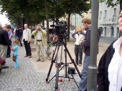 Kamera Leute  und im Hindergrund  Menschen