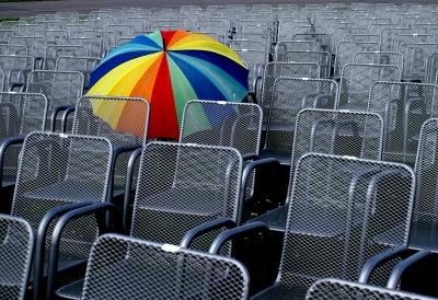 leere Stuhlreihen mit buntem Schirm