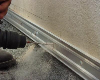 Bohrvorgang beim Schienenverlegen Flachdach