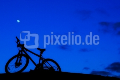 Silhouette eines Fahrrades bei Nacht (blauer Hintergrund)