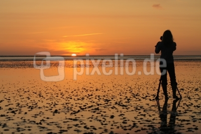 Fotografin beim Sonnenuntergang am Wattenmeer