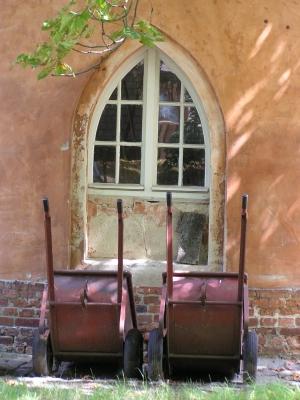Schubkarren vor neogotischem Fenster