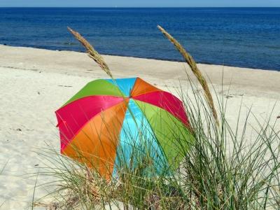 Einsamer Sonnenschirm am menschenleeren Strand