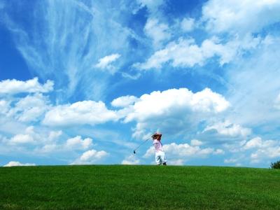 Golferin beim Abschlag vor Wolkenhimmel