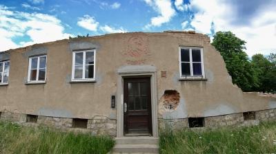 Fassade eines teilweise abgerissenes Hauses mit Eingangstür