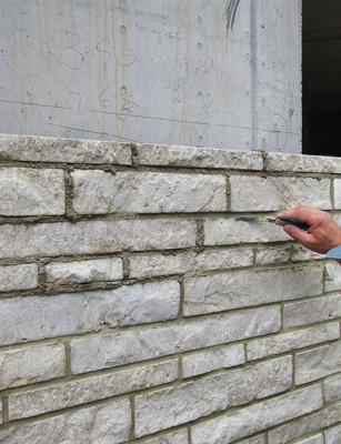 Bauen - Natursteinvorsatzwand wird verfugt
