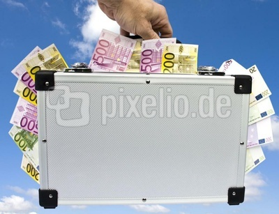 Geldkoffer in der Hand vor Wolkenhintergrund