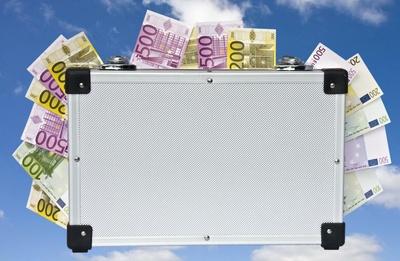 Geldkoffer vor Wolkenhintergrund