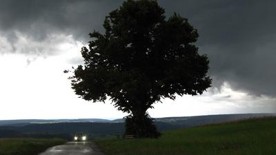 Dunkle Wolken mit PKW und Baum