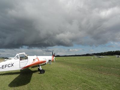 Motorflugzeug auf Grasbahn + Segelflugzeuge