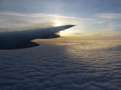 Jumbotragfläche über den Wolken gegen die Sonne