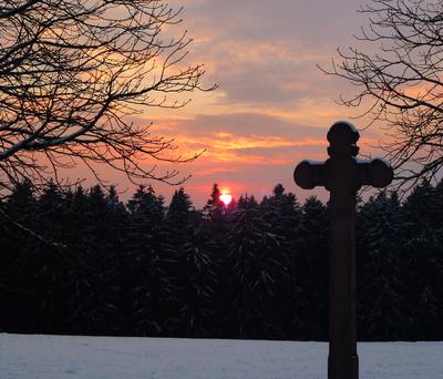 Kreuz mit Wald und Sonnenuntergang im Winter