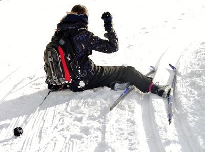 Skifahrerin sitzt in der Loipe