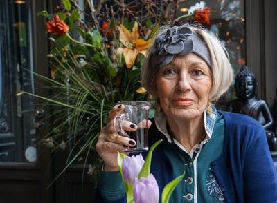 Seniorin mit Glühwein im Cafe