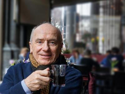 Senior mit Glühwein im Cafe