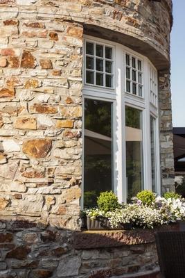 Naturstein-Turm mit Rundfenster