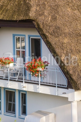 Reetdach-Haus mit Balkon und Blumen
