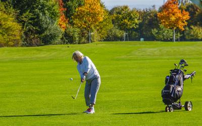 Seniorin beim Golfspiel