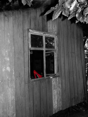 Roter Schuh im alten Fenster