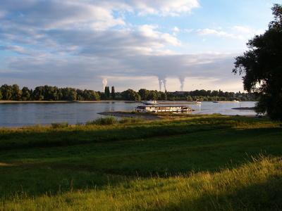 Niederrheinische Auenlandschaft mit Braunkohle-Kraftwerksschloten im Hintergrund