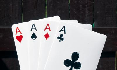 Poker - Vier Asse vor Holzwand