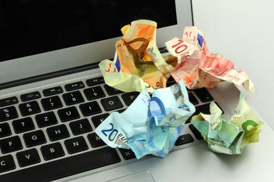 Zerknülltes Geld auf Laptop