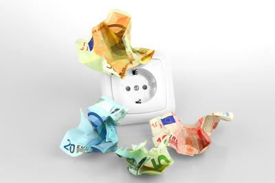 Zerknülltes Geld mit Steckdose