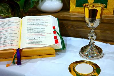 Kelch, Hostie und Messbuch auf dem Altar