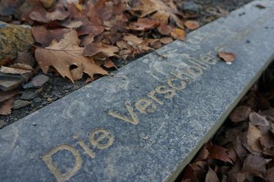 Inschrift in einem Stein im Boden einer Berghalde.