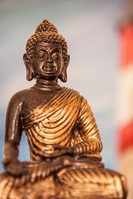 Buddha mit Leuchtturm im Hintergrund