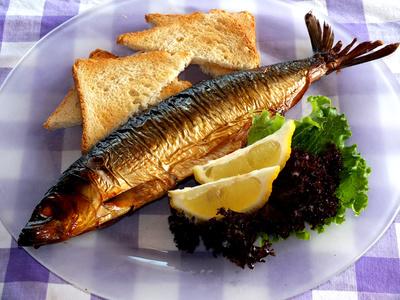Geräucherte Fisch auf Teller mit Toastbrot und Beilagen
