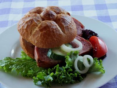Leberkäsesemmel auf Teller mit Salat,Tomate und Zwiebeln