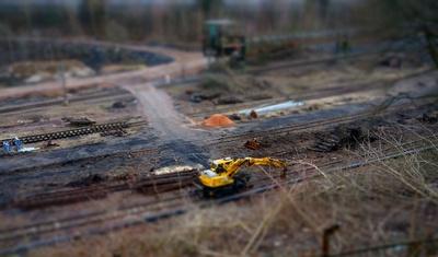 Miniaturaufnahme, Bagger auf Industriegelände, Tilt-Shift