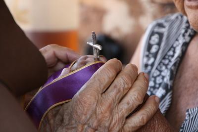 Alte Hände umklammern das Kreuz