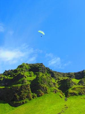 Grüne Felsen mit Paraglider