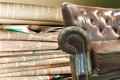 Zeitungsleser und Ledersessel