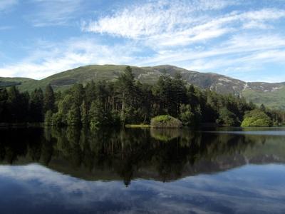 Berg & Waldlandschaft vor blauem See in Großbritannien