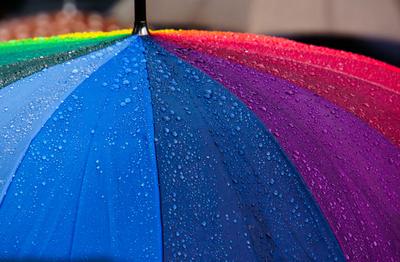 Regentropfen auf buntem Regenschirm