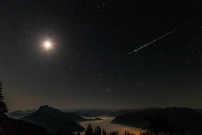 Meteorspur über Nebellandschaft.