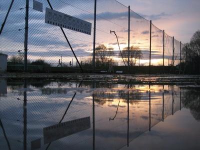 Tennisplatz nach Regenschauer und Sonnenuntergang