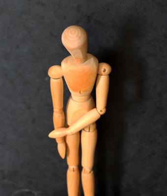 Holzfigur in trauriger Haltung