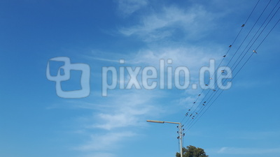 Strommast Überland mit Vögeln, Himmel und Wolken