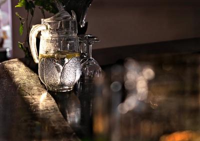 Zitronenwasser im Glaskrug auf alter Holztheke im Sonnenlicht