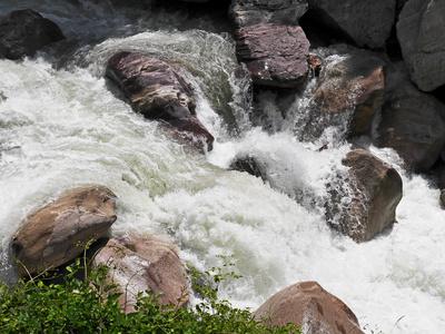 Alpenfluss im Felsbett