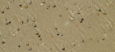 Ablaufendes Meerwasser über Steine und Sand