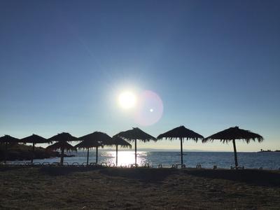 Griechenland: Sonnenschirme am Strand im Gegenlicht.