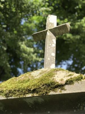 Kreuz auf altem Grabstein mit Moos